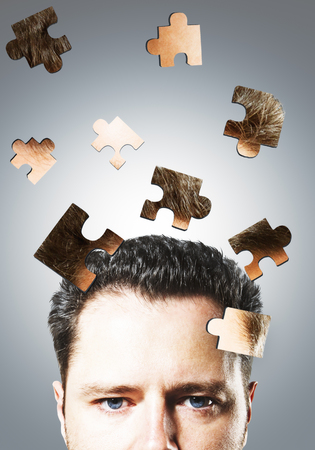 Puzzle headed businessman on gray background. Confusion and maze concept
