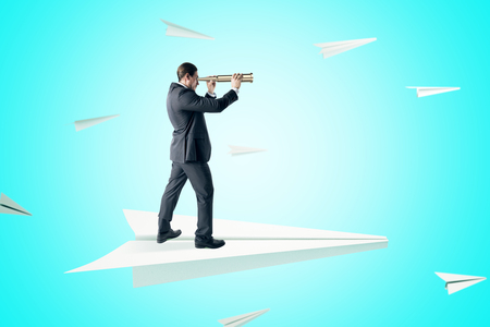 Businessman looking into the distance with binoculars while standing on abstract paper plane on blue background. Leadership and success concept