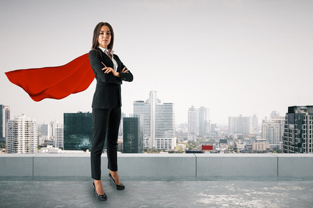 Attractive young european woman with red hero cape and folded arms standing on city background. Superhero and success concept
