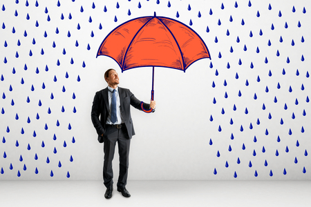 Businessman with abstract drawn rain and umbrella sketch. Protection and security concept