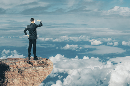 Back view of young businessman looking into the distance on cliff and beautiful sky background. Research and occupation concept