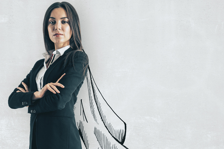 Portrait of attractive young european businesswoman with drawn cape on concrete wall background. Leadership and success concept