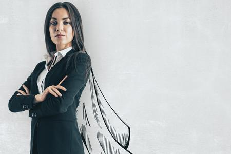 Portret van aantrekkelijke jonge Europese zakenvrouw met getekende cape op betonnen muur achtergrond. Leiderschap en succes concept Stockfoto