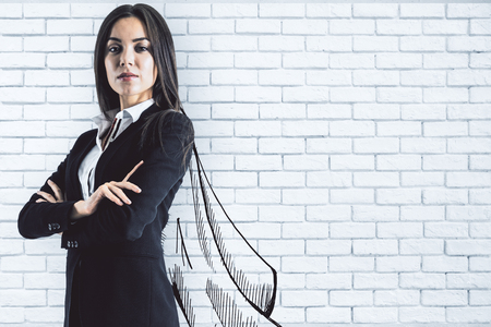 Portrait of attractive young european businesswoman with drawn cape on brick wall background. Leadership and leader concept Stockfoto - 107404891