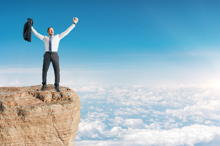 Businessman celebrating success on cliff edge. Sky background. Leadership and winner concept