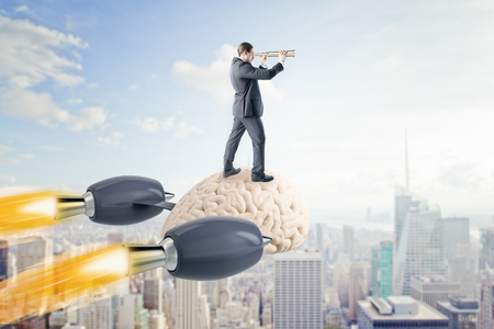 Businessman looking into the distance on abstract launching brain rocket. Sky and city background. Brainstorm and research concept. 3D Rendering