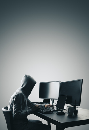 Hacker using computers at dark desk. Hacking and thief concept