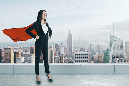 Smiling super hero woman with red cape standing on rooftop with city view and daylight. Confidence and leadership concept Stockfoto