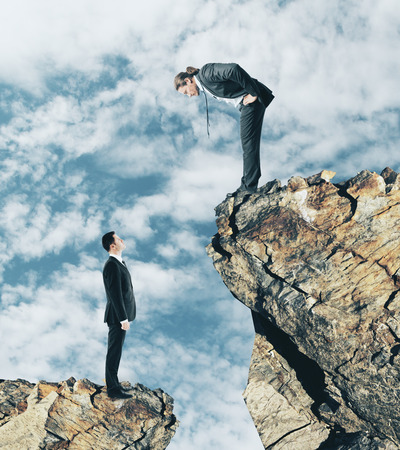 Two businessmen on different cliff levels looking at each other. Supervision and boss concept