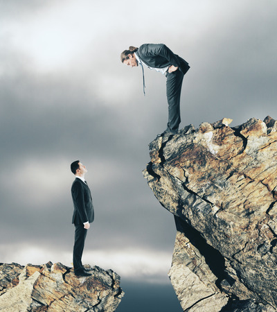 Two businessmen on different cliff levels looking at each other. Supervision and leadership concept