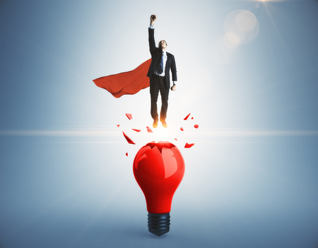 Businessman with red hero cape launching from abstract broken lamp. Gray background. Startup and idea concept