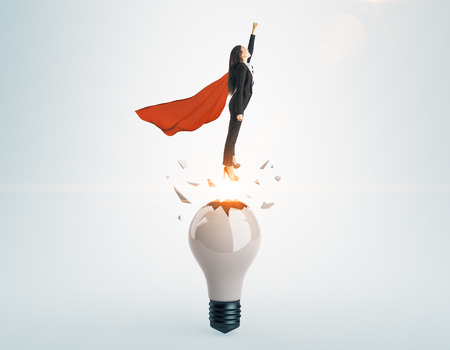 Businesswoman with red hero cape launching from abstract broken lamp. Gray background. Startup and freedom concept