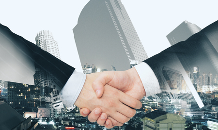 Close up of handshake on abstract city background. Teamwork and union concept. Double exposure Stock fotó