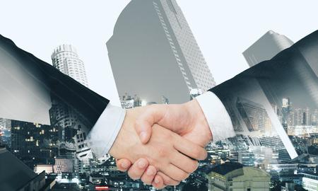 Gros plan de la poignée de main sur fond de ville abstraite. Concept de travail d'équipe et d'union. Double exposition