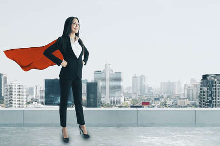Smiling super hero woman with red cape standing on rooftop with city view and daylight. Confidence and security concept Stockfoto