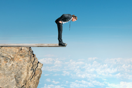 Businessman looking down from mountain top on sky background. Success and altitude concept