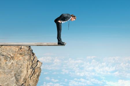 Uomo d'affari guardando giù dalla cima della montagna sullo sfondo del cielo. Successo e concetto di altitudine