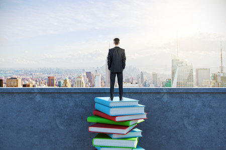 Back view of young businessman standing on rooftop with book stack and city view. Research and education concept Banco de Imagens