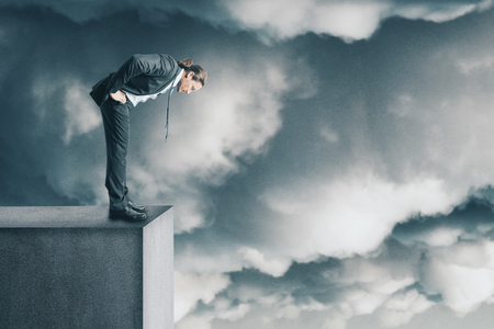 Risk and future concept. Young businessman looking down from rooftop. Sky background