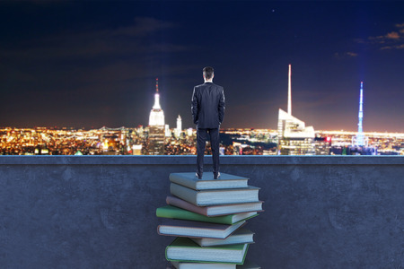 Back view of young businessman standing on rooftop with book stack and night city view. Research and knowledge concept Stock Photo