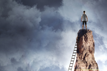 Man on cliff with ladder on sky background. Research and challenge concept