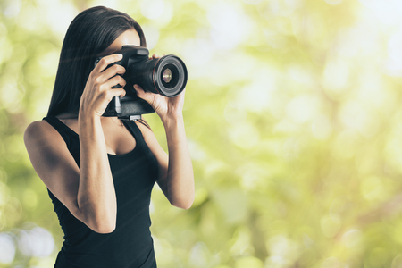 Attractive young european woman taking photograph with professional camera on blurry green background. Hobby and occupation concept