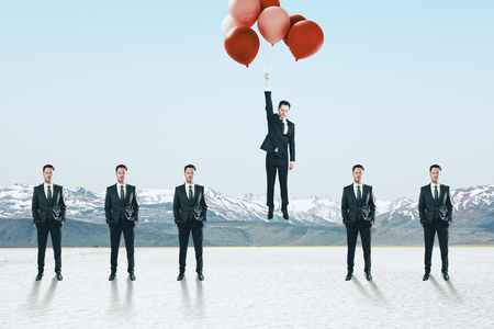 Businessmen looking at man flying with balloons. Freedom and success concept