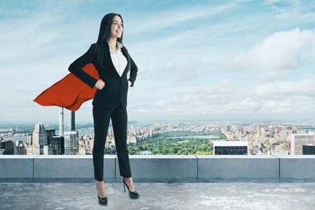 Smiling superhero woman standing on concrete rooftop with city view. Success and leadership concept