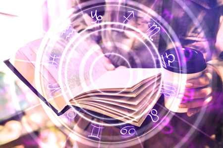Close up of hands holding abstract book with zodiac wheel. Magic and astrology concept. Double exposure