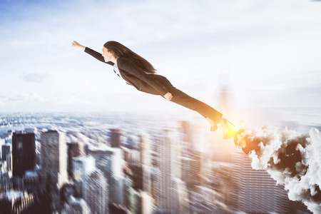 Abstract super hero businesswoman on blurry city background. Leadership and confidence concept