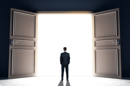 Businessman standing in front of wide open bright opportunity door. Success and dream concept. 3D Rendering