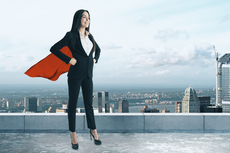 Smiling superhero woman standing on concrete rooftop with city view. Power and leadership concept