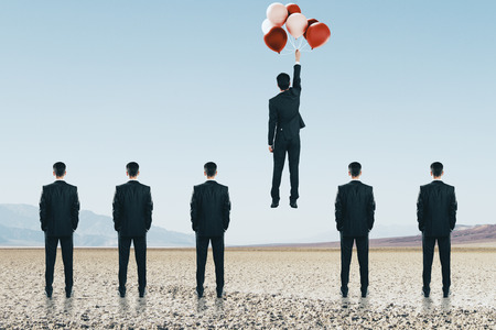 Businessmen looking at man flying with balloons. Freedom and teamwork concept 版權商用圖片