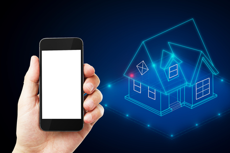 Hand holding cellphone with glowing blue house hologram. Smart home concept. Mock up Stock Photo