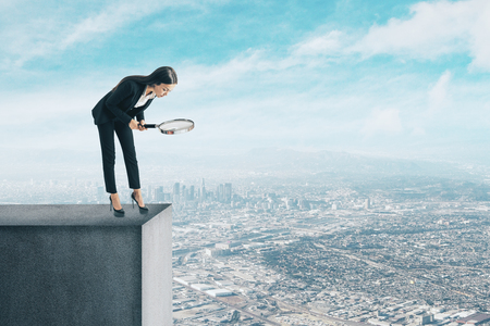 Businesswoman with magnifier looking down from rooftop. City background. Research and abyss concept