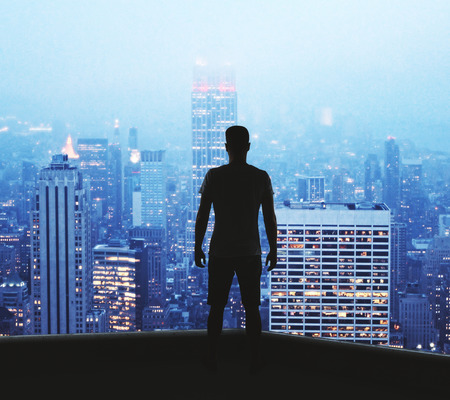 Back view of young backlit man looking into the distance on illuminated New York city backdrop. Research and occupation concept