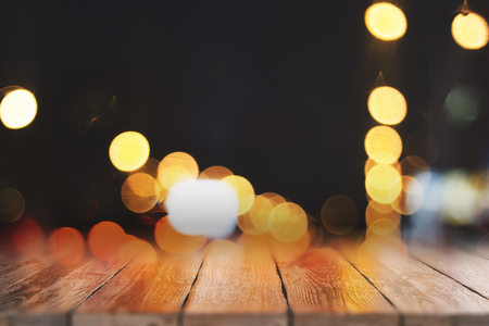 Abstract blurry wooden desktop on blurry bokeh lights background. Montage concept Standard-Bild