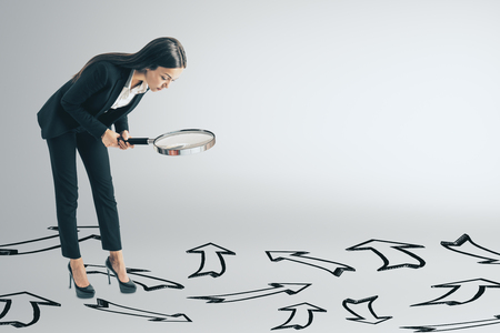 Young businesswoman using magnifier to look at arrows on ground. Different direction and research concept