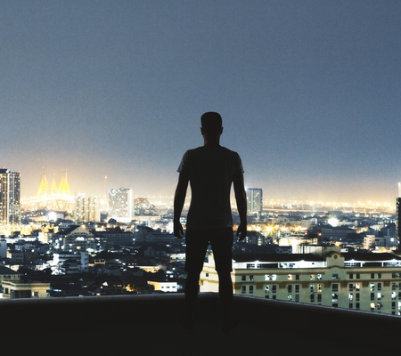 Back view of young backlit man looking into the distance on illuminated New York city background. Research and occupation concept