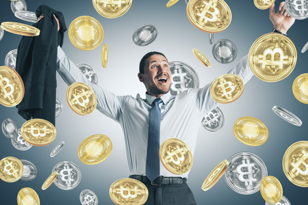 Happy young european businessman with creative shiny bitcoin rain on gray background. Cryptocurrency and finance concept Archivio Fotografico - 108748212