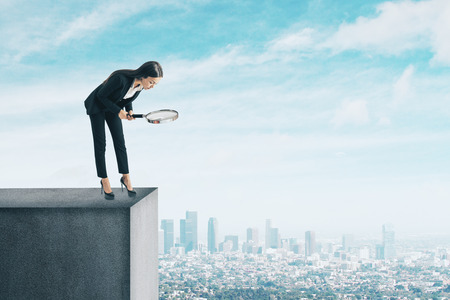 Businesswoman with magnifier looking down from rooftop. City background. Research and challenge concept