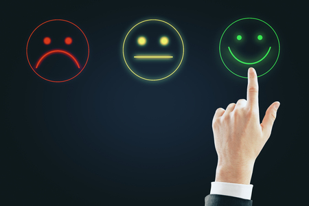 Hand with smiley rating on dark background. Excellent service concept Stockfoto