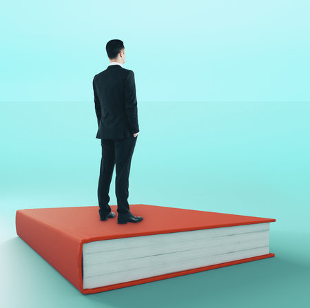Young businessman looking into the distance while standing on book. Job search and wisdom concept Stock Photo