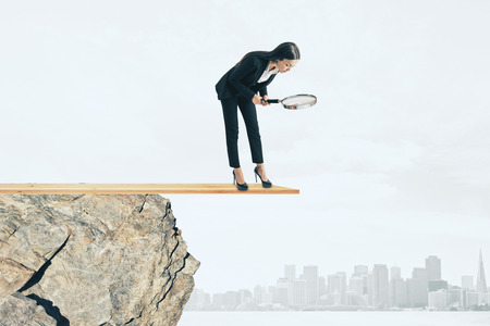 Businesswoman with magnifier looking down from cliff. City background. Research and risk concept 스톡 콘텐츠