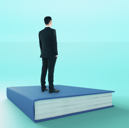Young businessman looking into the distance while standing on book. Research and wisdom concept Stock Photo
