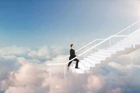 Young businessman climbing stairs on beautiful sky background with clouds. Career development and success concept