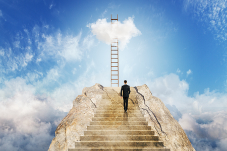 Young businessman climbing stairs on beautiful sky background with clouds. Career development and challenge concept