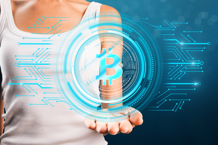 Woman hand holding bitcoin hologram on blurry blue background. E-commerce and crypto concept. Double exposure