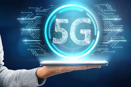 Close-up van hand met tablet met gloeiend 5G-pictogram op onscherpe blauwe achtergrond. Internetsnelheid en communicatieconcept. 3D-weergave Stockfoto