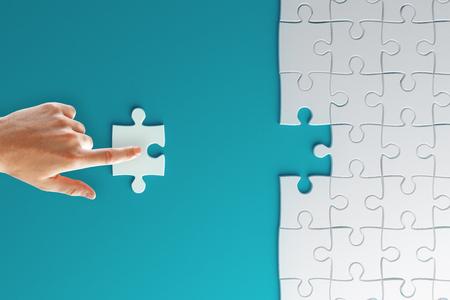 Sfondo creativo con pezzo di puzzle raccordo a mano. Jigsaw e concetto di lavoro di squadra. Rendering 3D Archivio Fotografico